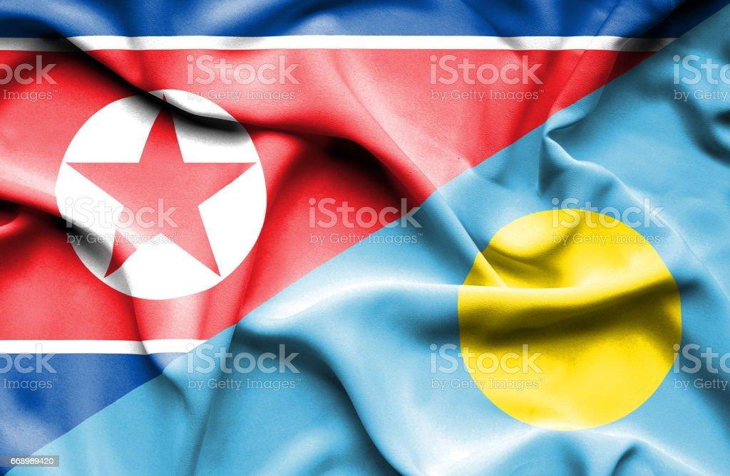 Waving flag of Palau and North Korea stock photo