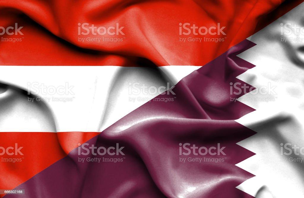 Waving flag of Qatar and Austria stock photo