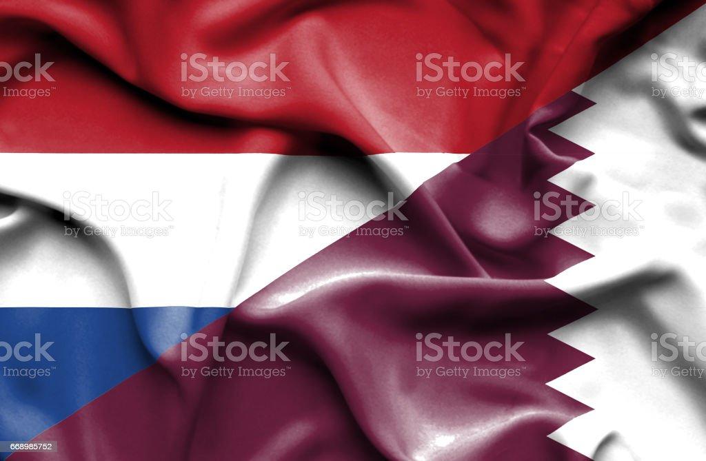 Waving flag of Qatar and Netherlands stock photo