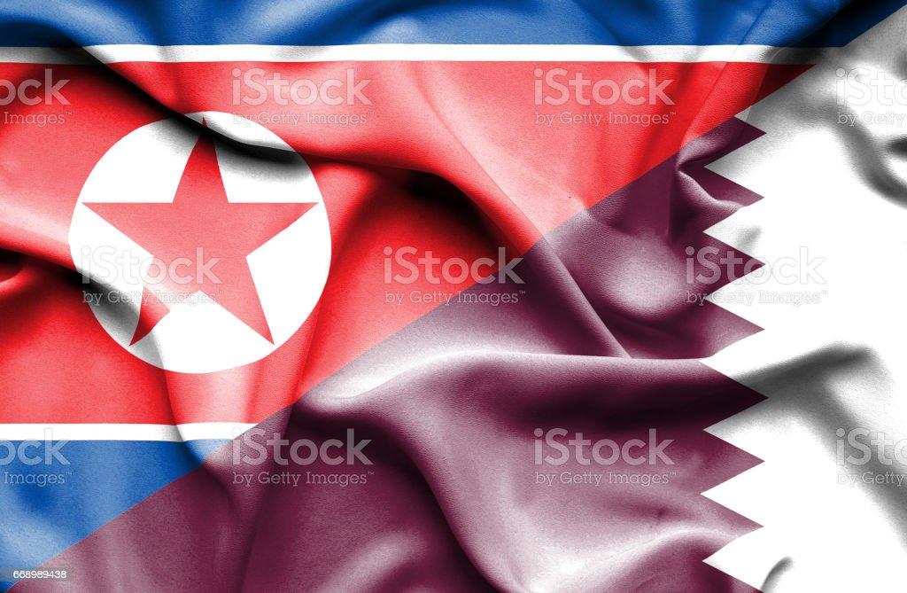 Waving flag of Qatar and North Korea stock photo