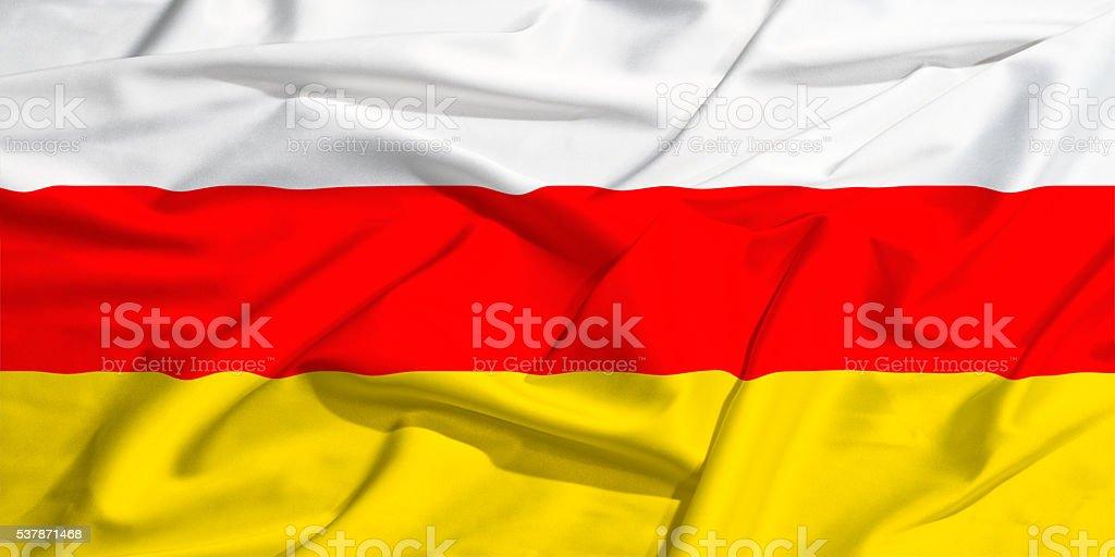 waving flag of South Ossetia on a silk bright drape stock photo