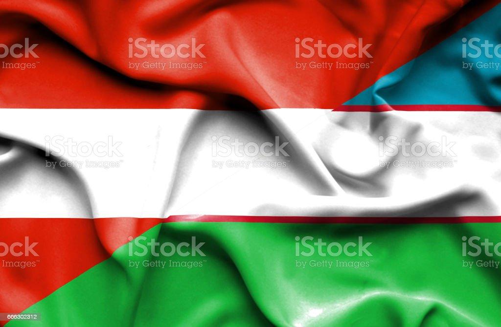 Waving flag of Uzbekistan and Austria stock photo