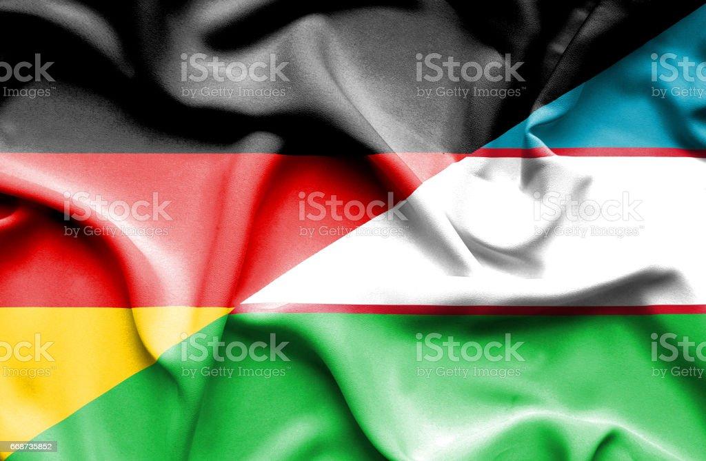 Waving flag of Uzbekistan and Germany stock photo