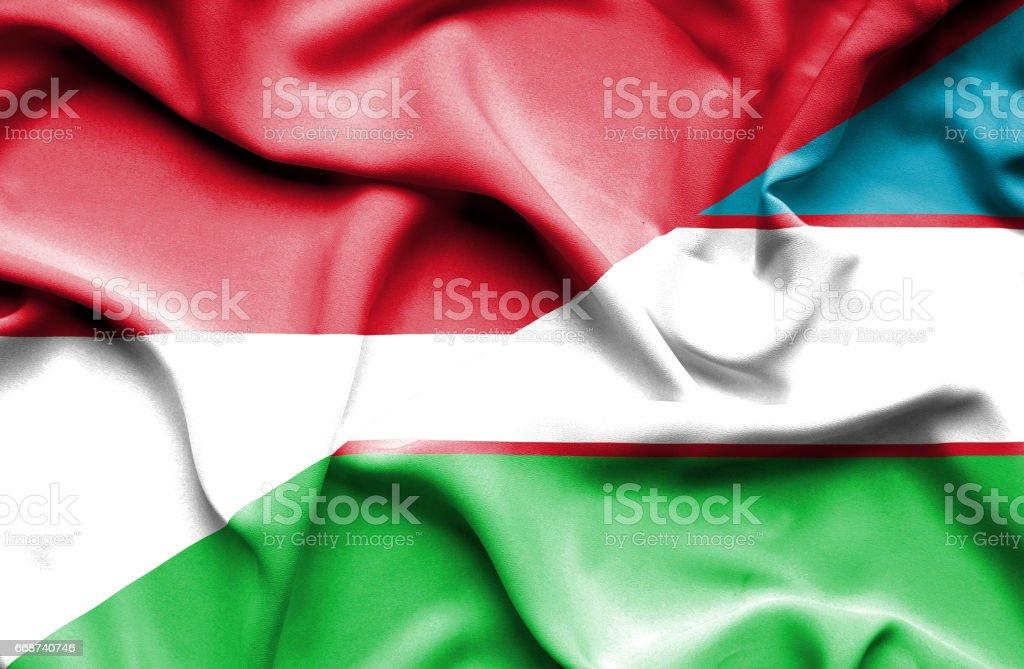 Waving flag of Uzbekistan and Indonesia stock photo