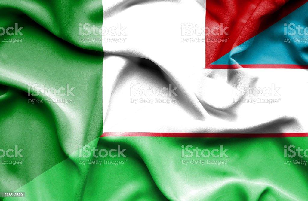 Waving flag of Uzbekistan and Italy stock photo