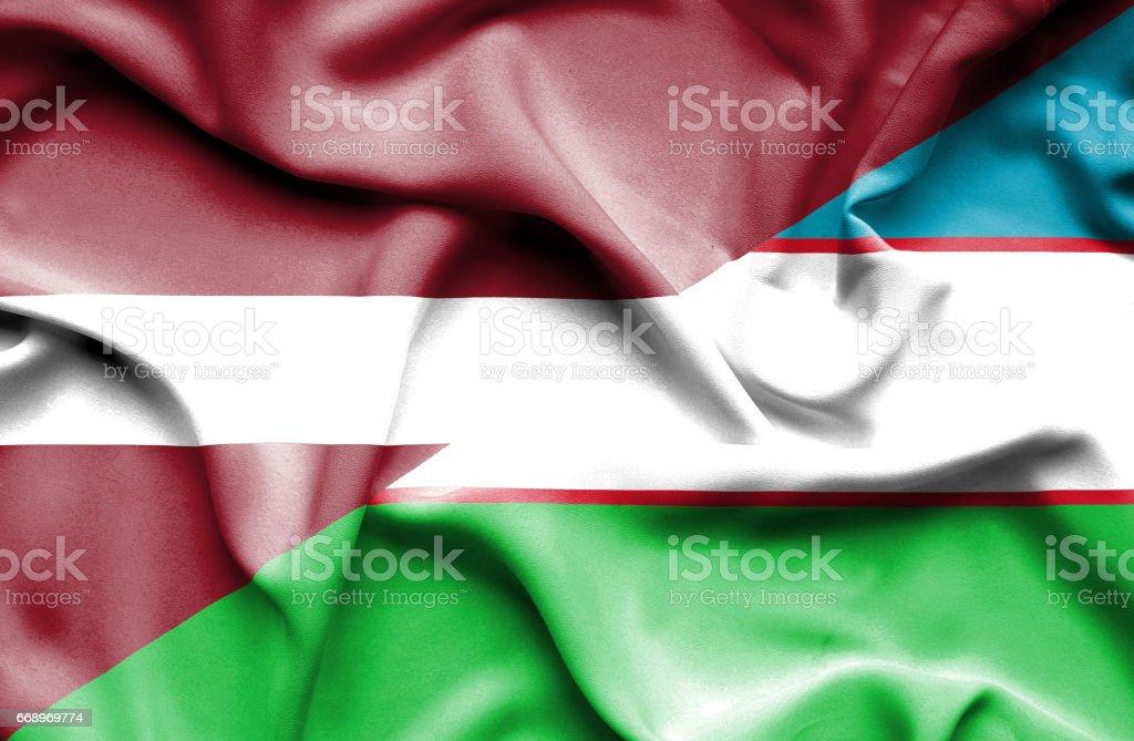 Waving flag of Uzbekistan and Latvia stock photo
