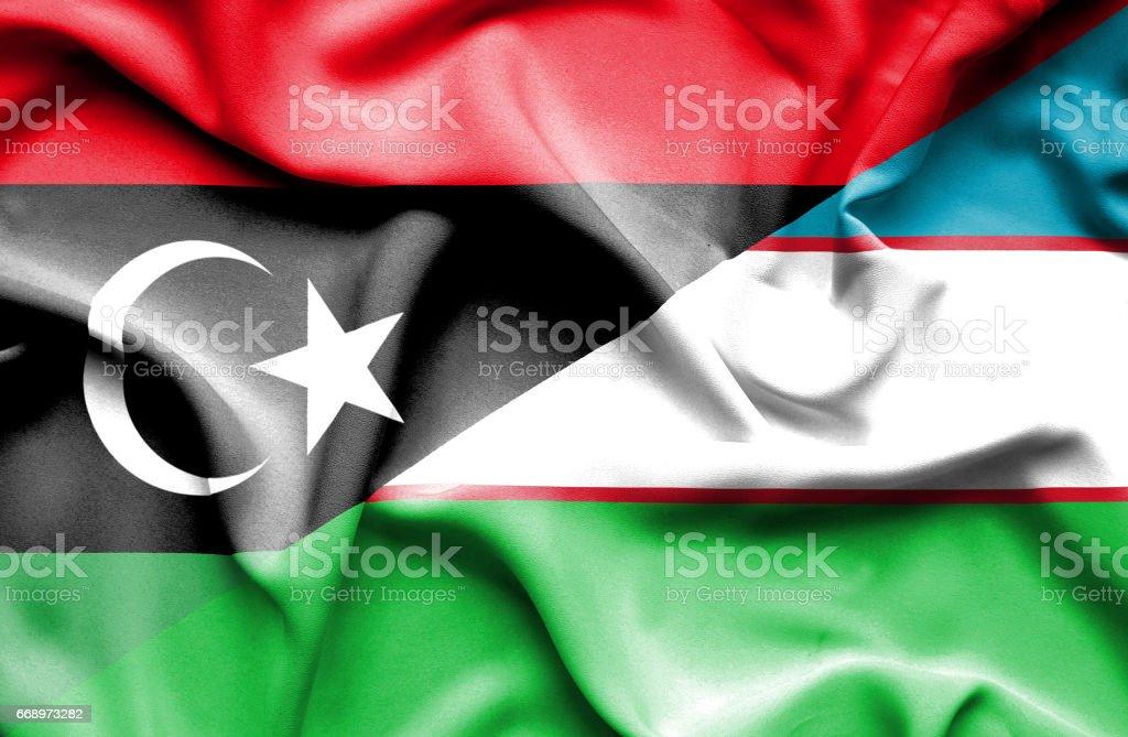 Waving flag of Uzbekistan and Libya stock photo