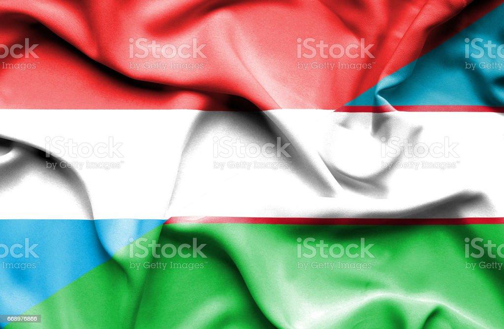 Waving flag of Uzbekistan and Luxembourg stock photo
