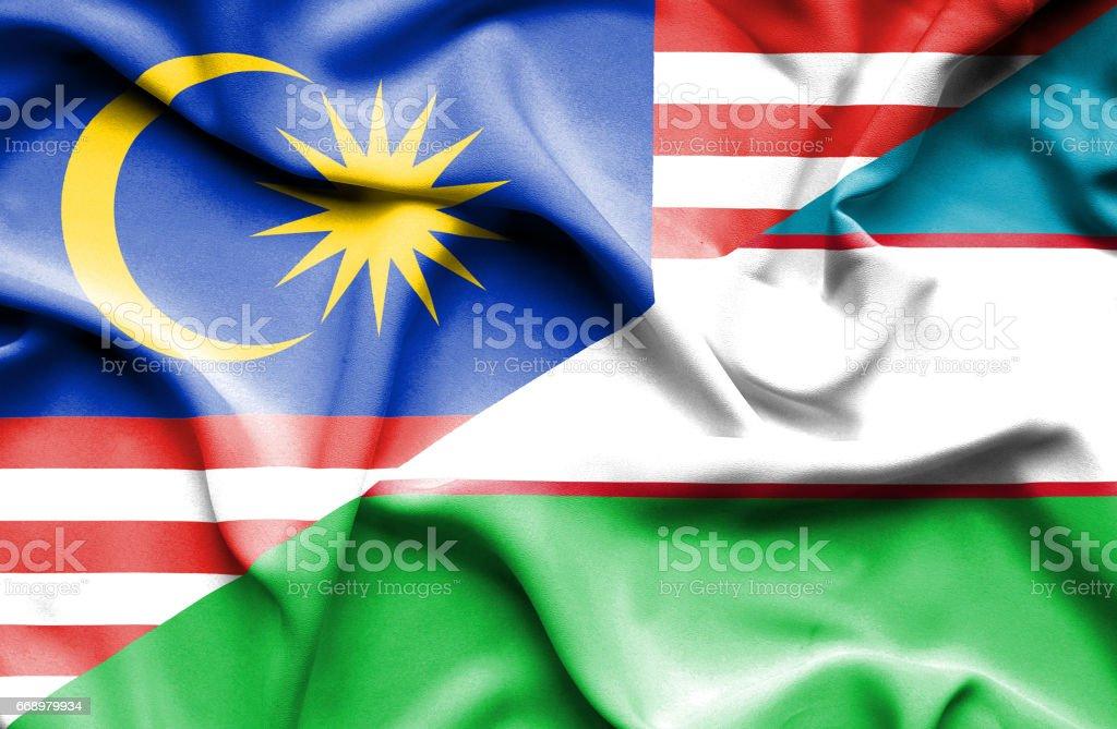 Waving flag of Uzbekistan and Malaysia stock photo