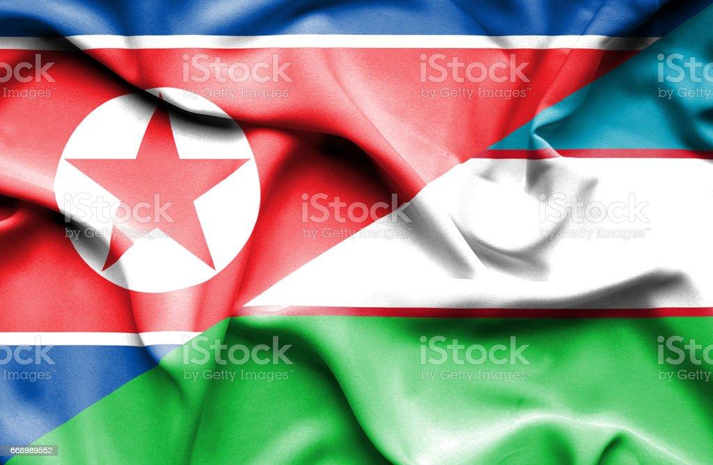 Waving flag of Uzbekistan and North Korea stock photo