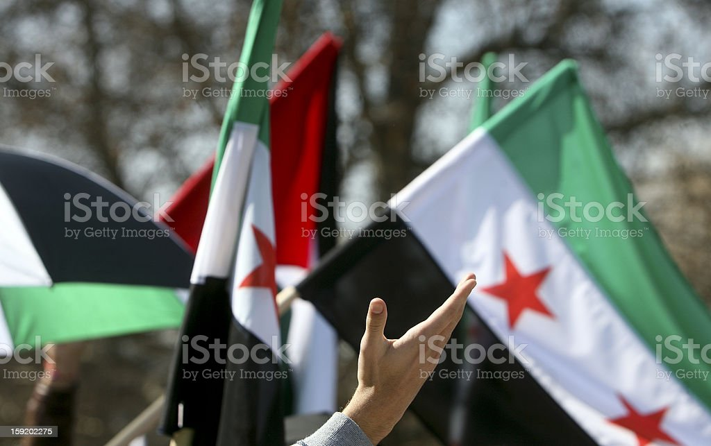 Waving hand Syrian flags stock photo