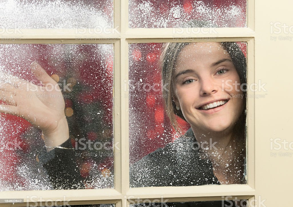waving happy young woman looking through snowy window at Christmas stock photo