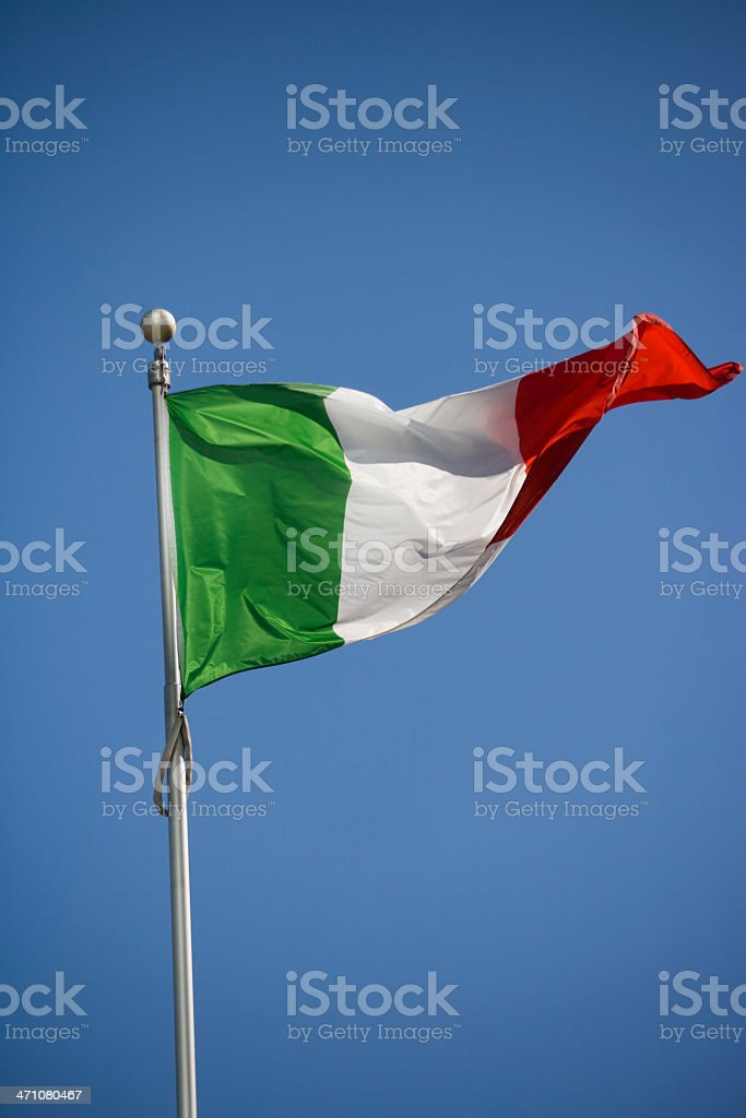 A waving Italian flag on a flagpole under blue sky royalty-free stock photo