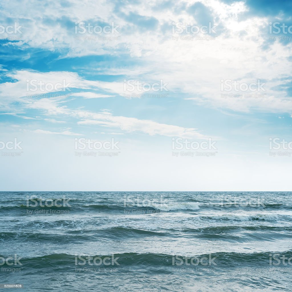 waving sea and cloudy sky with sun over it stock photo