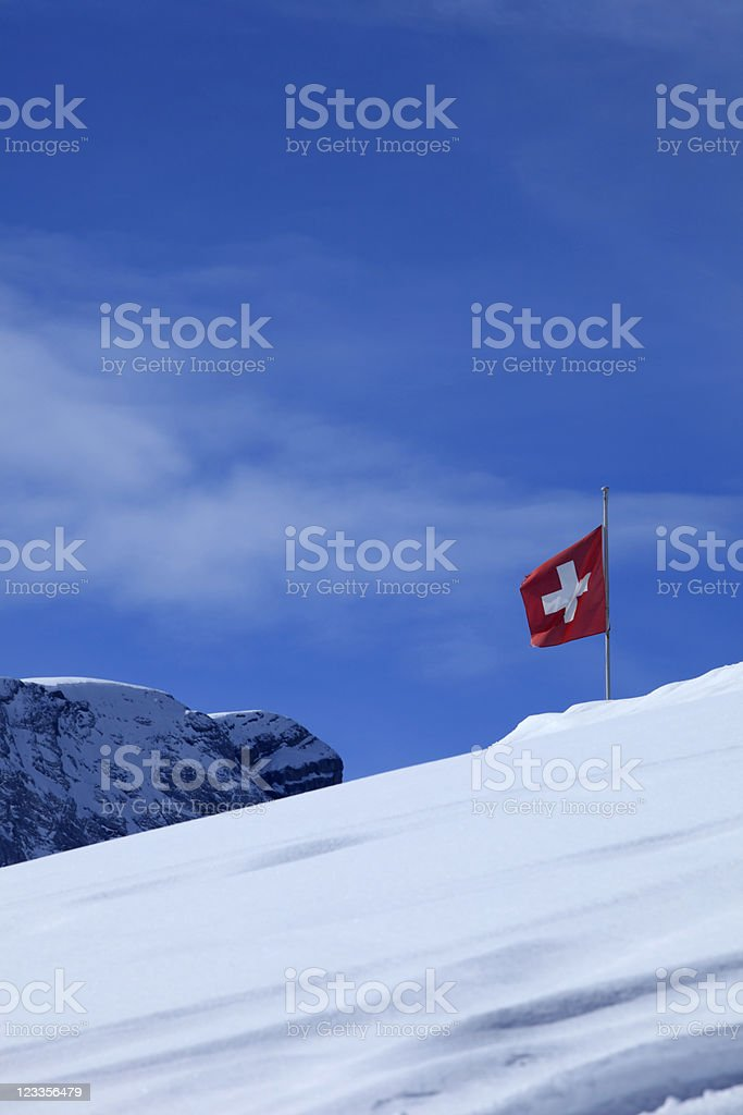 waving Swiss flag against a clear blue sky royalty-free stock photo