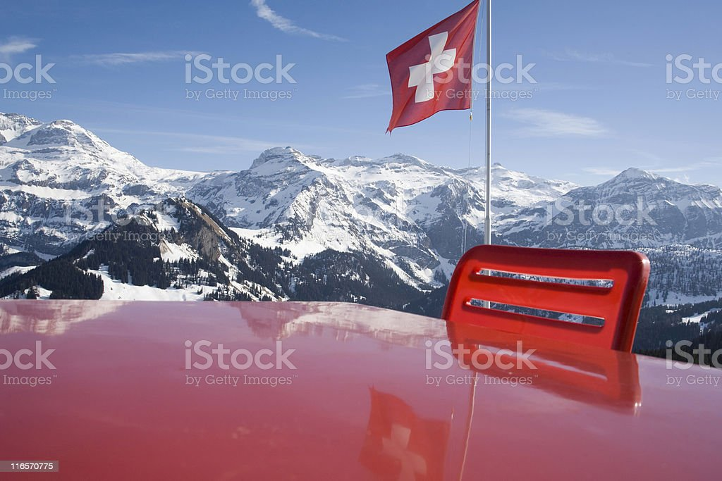 waving Swiss flag in the mountains stock photo