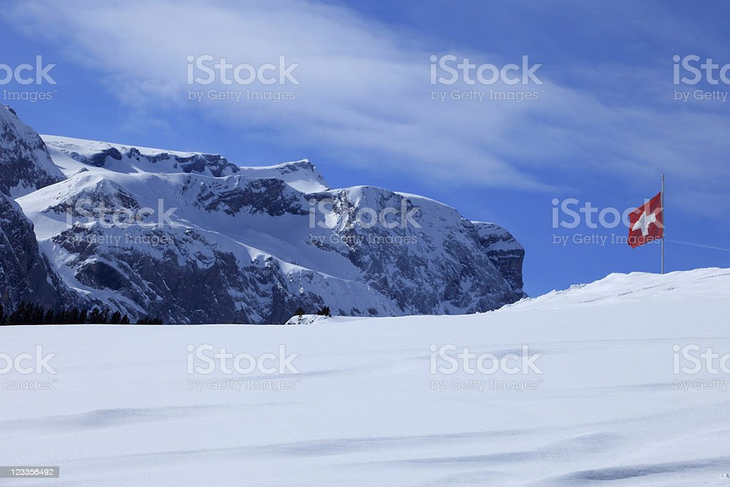 waving Swiss flag in the snow-covered Alps royalty-free stock photo
