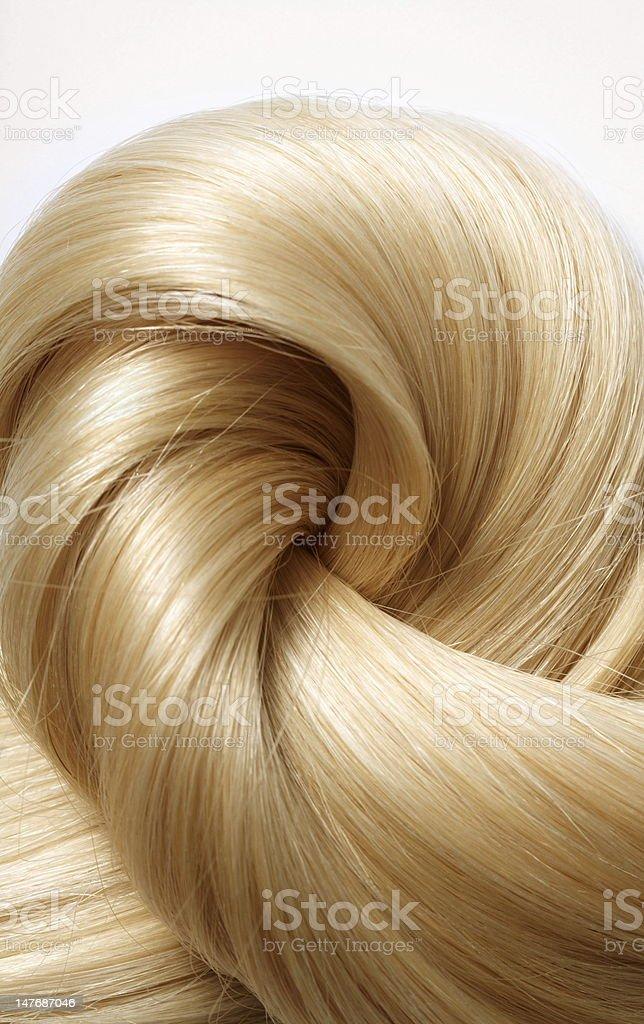 Wavy blonde hair spiraling in on itself stock photo
