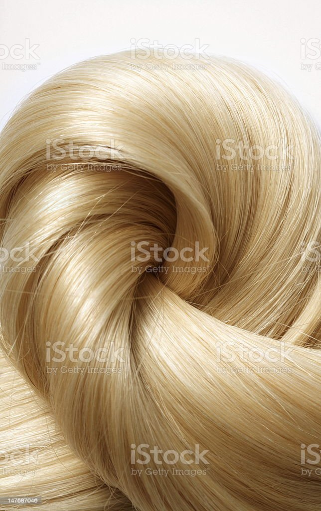 Wavy blonde hair spiraling in on itself stock photo