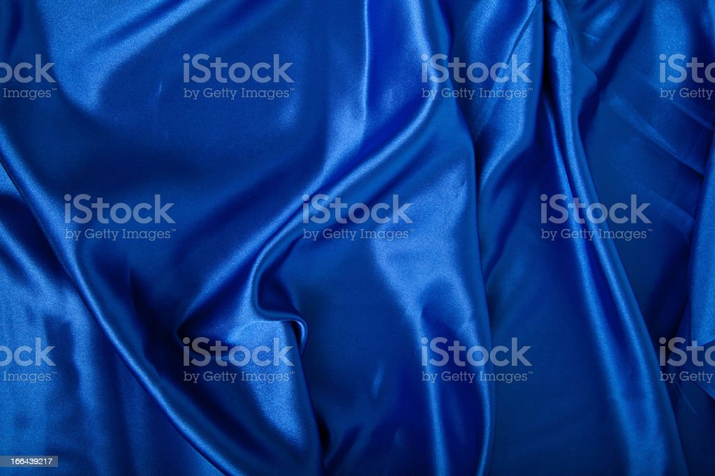 Wavy, blue silk fabric as a background royalty-free stock photo