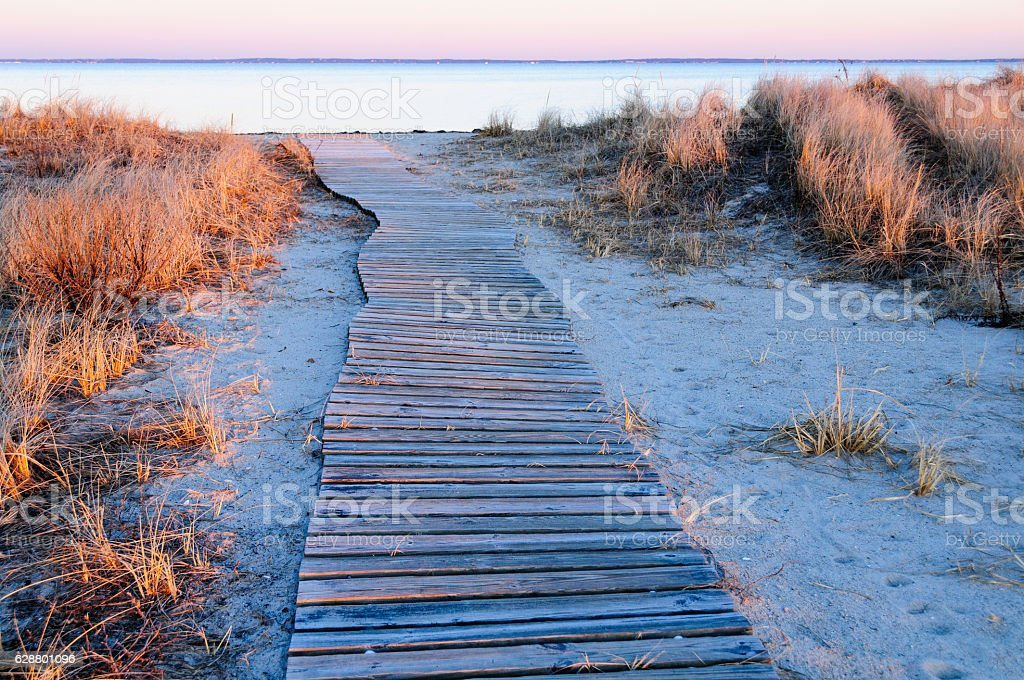 Wavy boardwalk across small dune stock photo