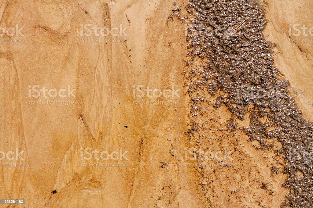 Wavy sand with silt on the beach after the backwash stock photo