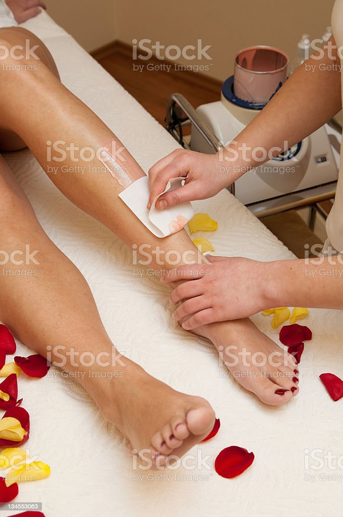 Waxing legs of a woman on a white table stock photo