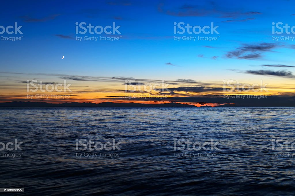 waxing moon after sunset over sea stock photo