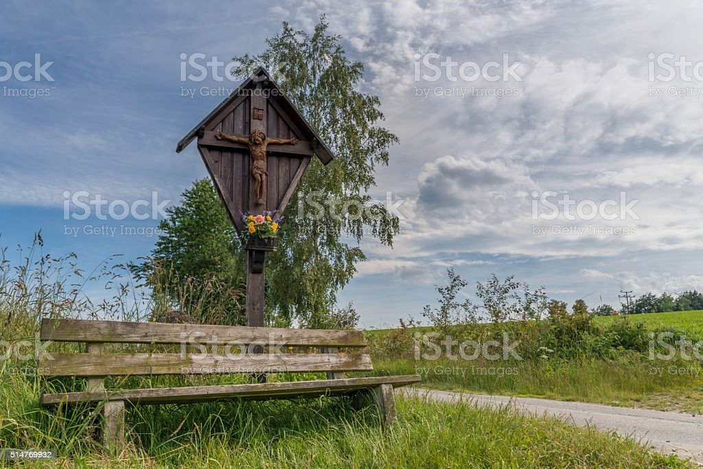 Wayside cross and wooden bench in the Bavarian forest stock photo