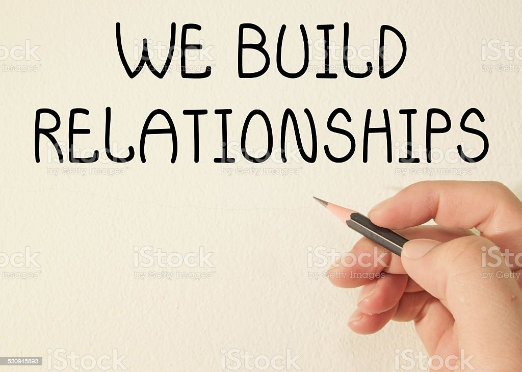 we build relationships text write on wall stock photo