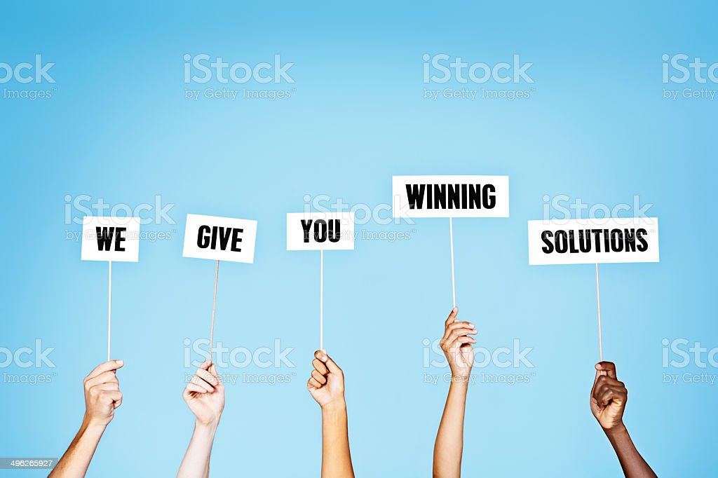 'We give you winning solutions' say hand-held words. stock photo
