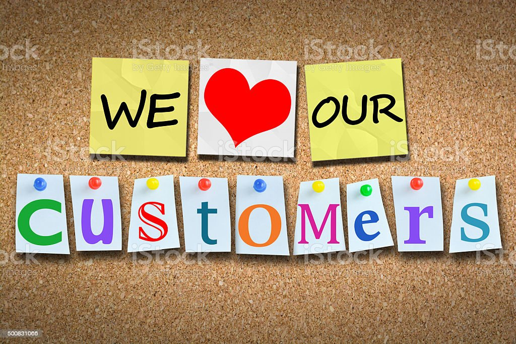 We love our customers on wooden cork billboard with pins stock photo