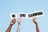 'We love teamwork' say hand-held signs on blue