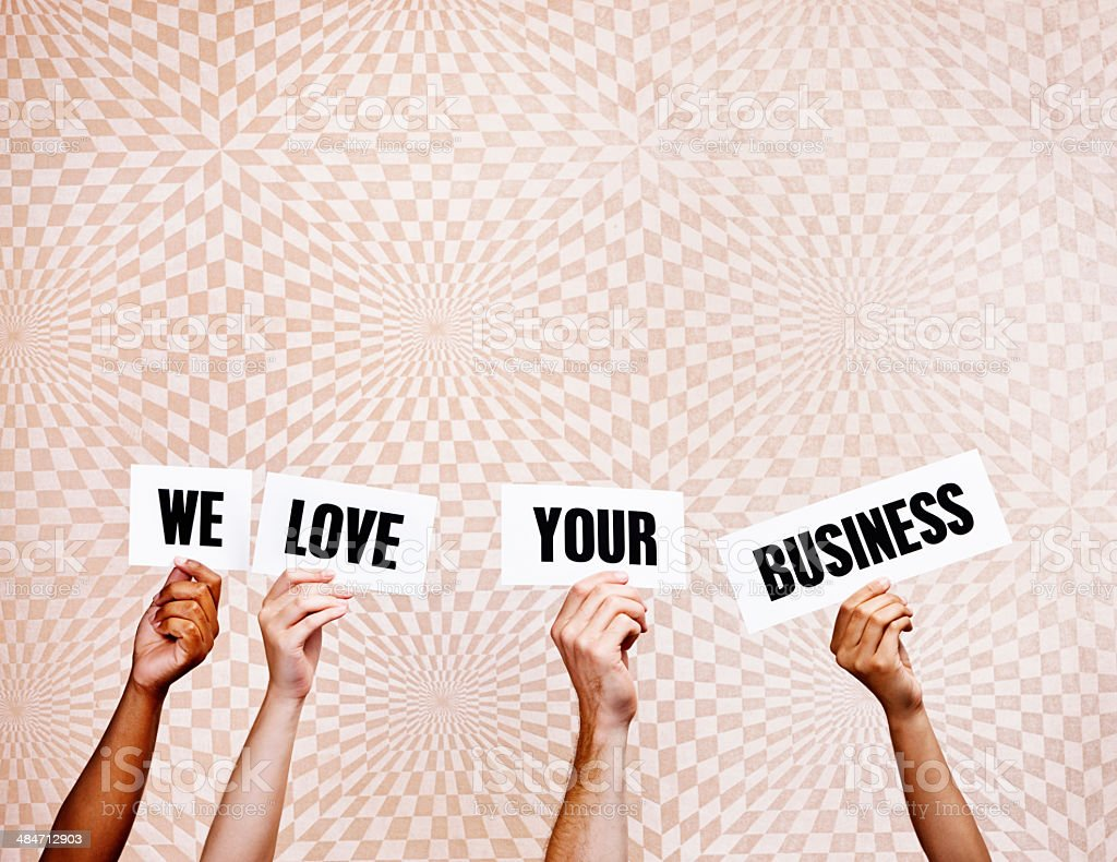 'We love your business' say hand-held words. Good news! stock photo
