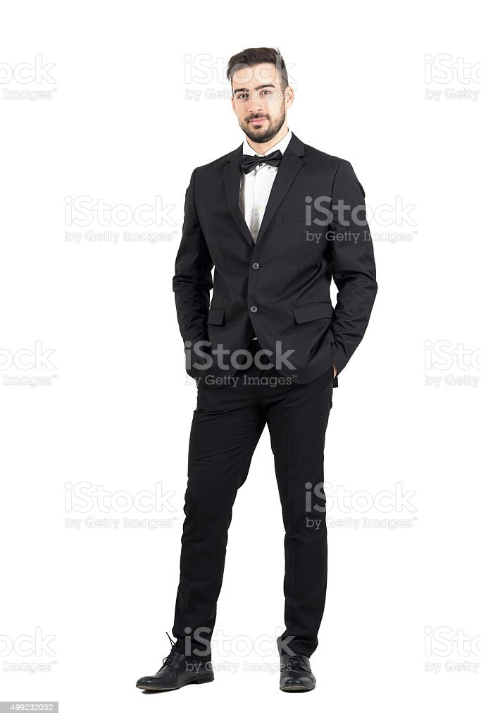 Wealthy confident relaxed young man in tuxedo looking at camera stock photo