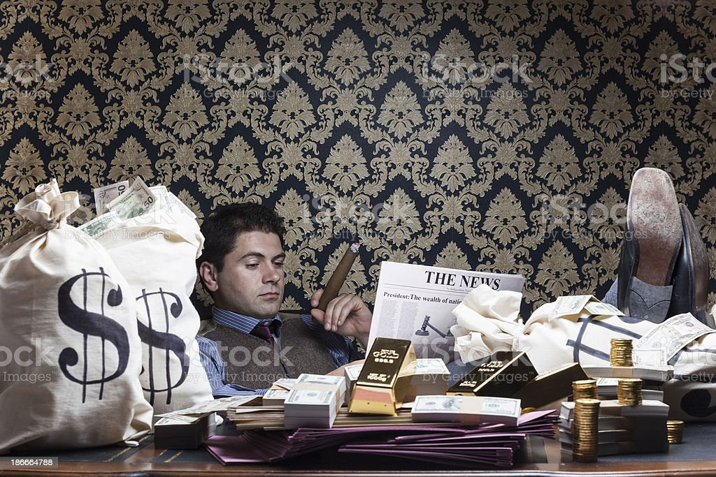 Wealthy man reading newspaper on desk royalty-free stock photo