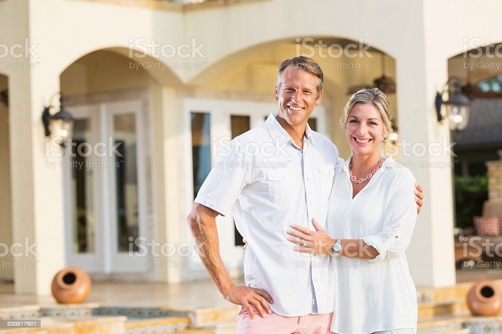 Wealthy mature couple outside their luxury home stock photo