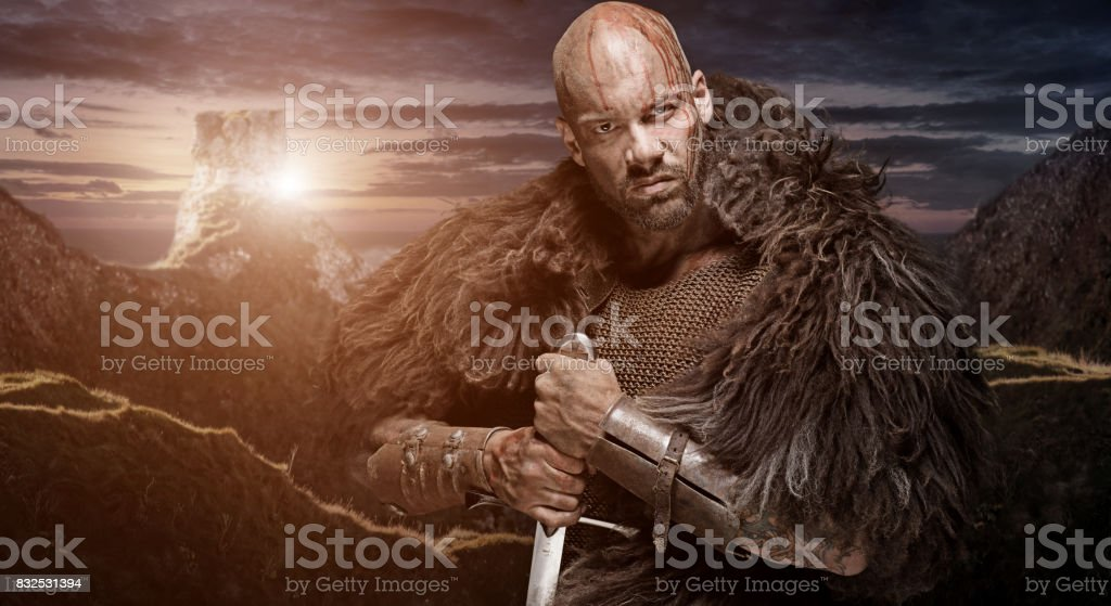 Weapon wielding bloody viking warrior in emotional pose stock photo