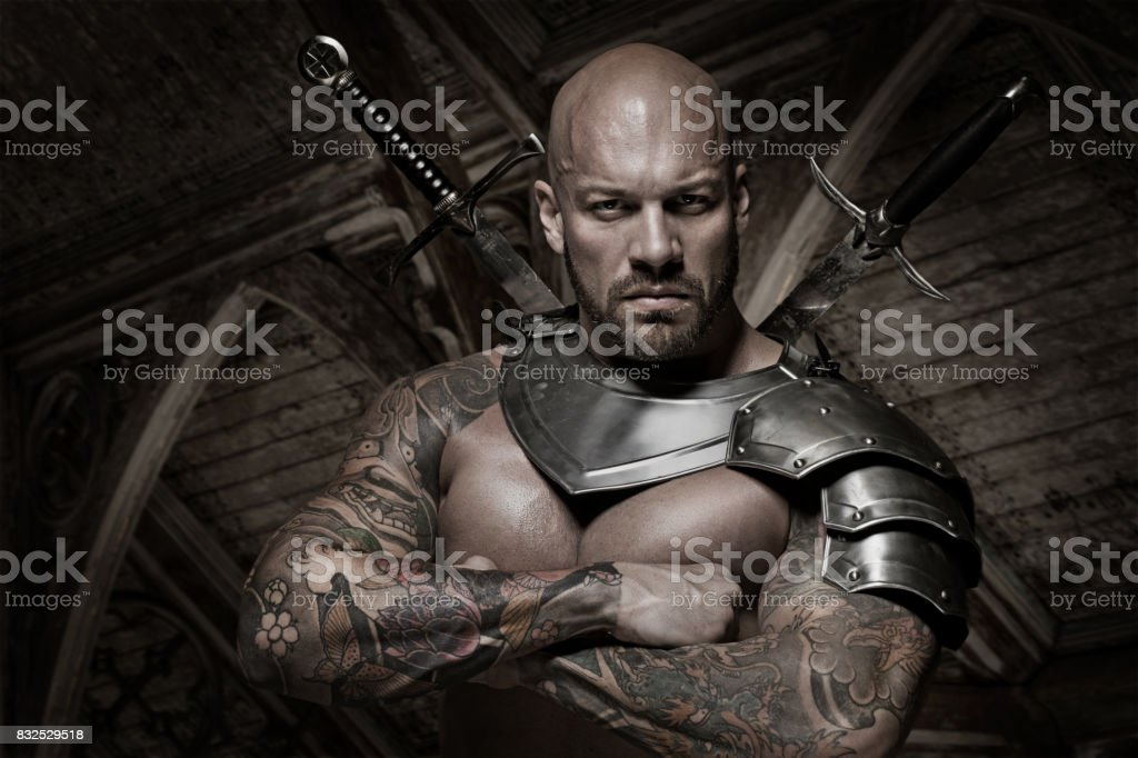 Weapon wielding male bald warrior in emotional pose stock photo