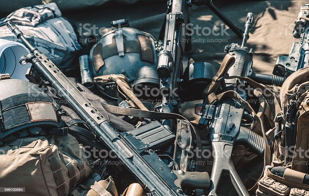 Weapons and protective clothes folded on the ground. stock photo