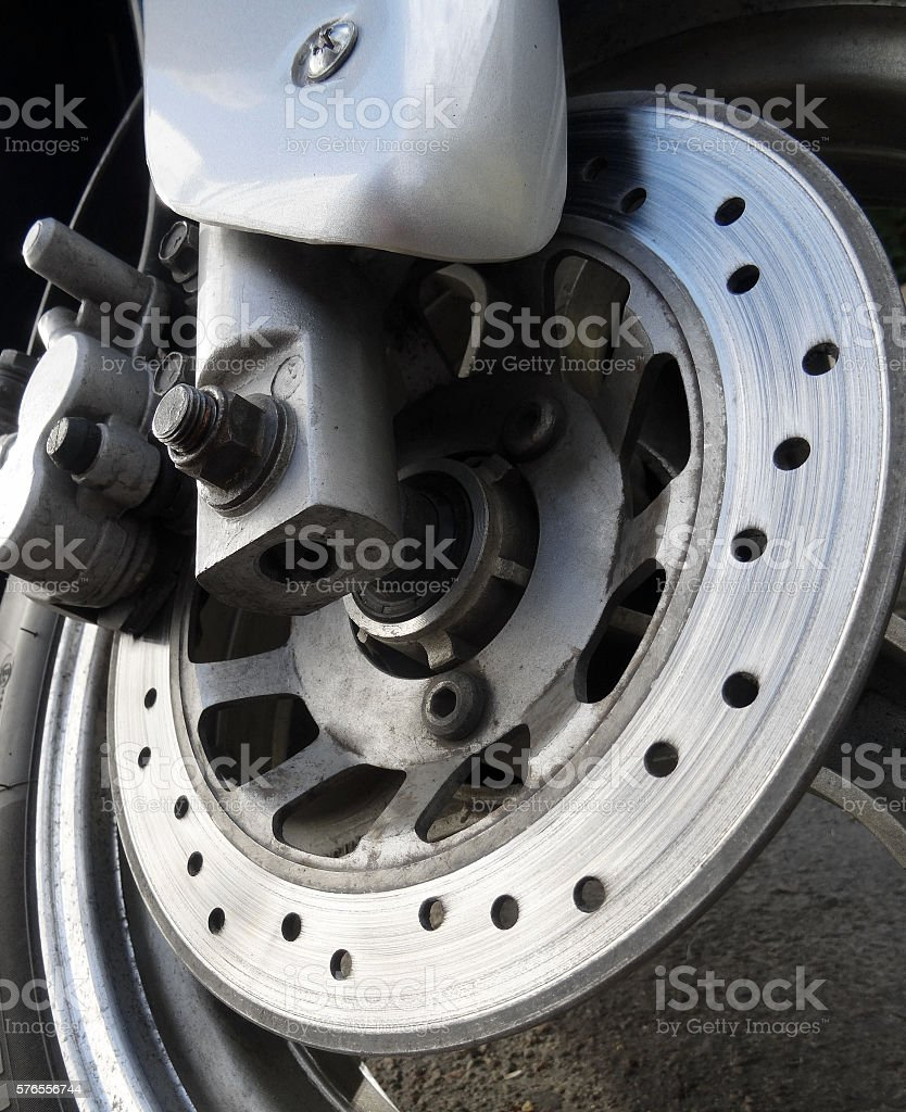 Wear brake disc on the front wheel of motorcycle stock photo