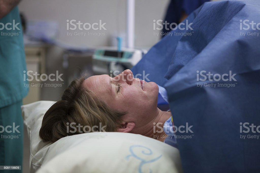 Weary mother lies in anticipation before her Caesarian Section stock photo