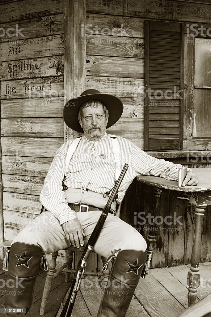 Very somber and tired Caucasian man with sheriff badge sitting on...