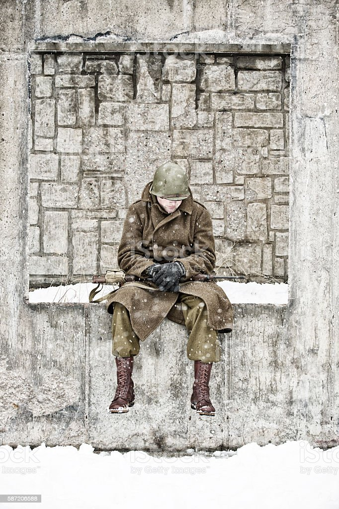 Weary WWII GI Sitting on a Wall In A Courtyard stock photo