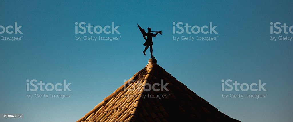 Weather vane in the form of trumpeting angel on roof stock photo