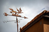 Weather vane on the roof and cloudy sky (vintage filter)