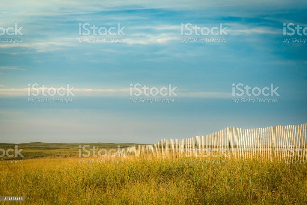 Weather worn fence on sandy beach stock photo