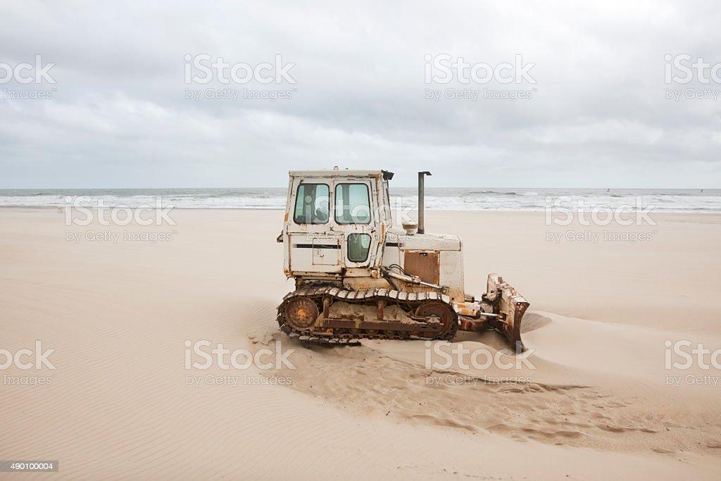 Weathered Bulldozer on Sandy Beach stock photo