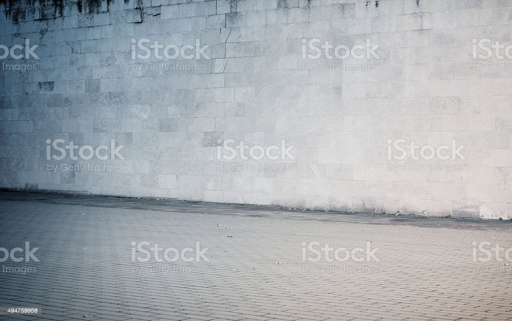 Weathered cinder block, brick wall texture with sidewalk stock photo