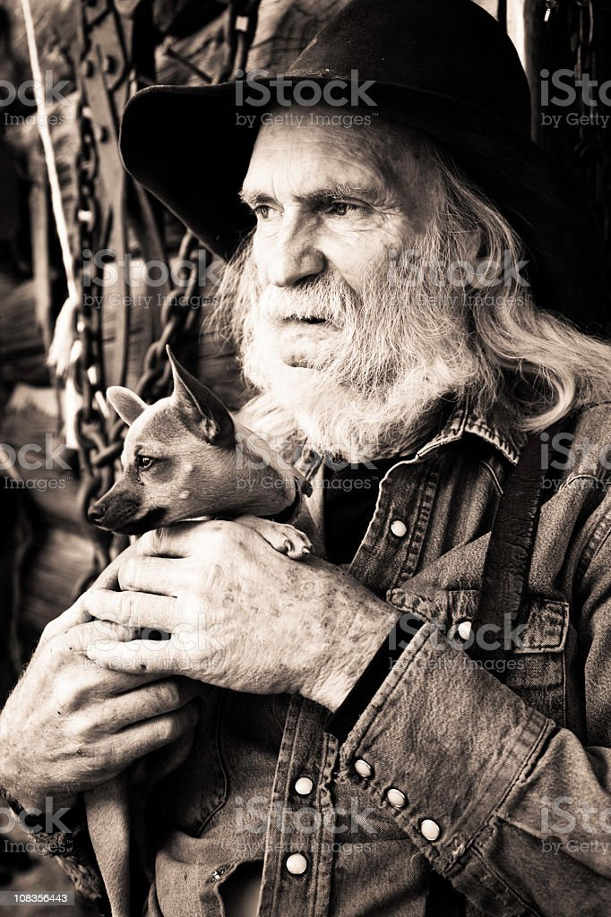 Weathered Cowboy with His Pet Dog royalty-free stock photo